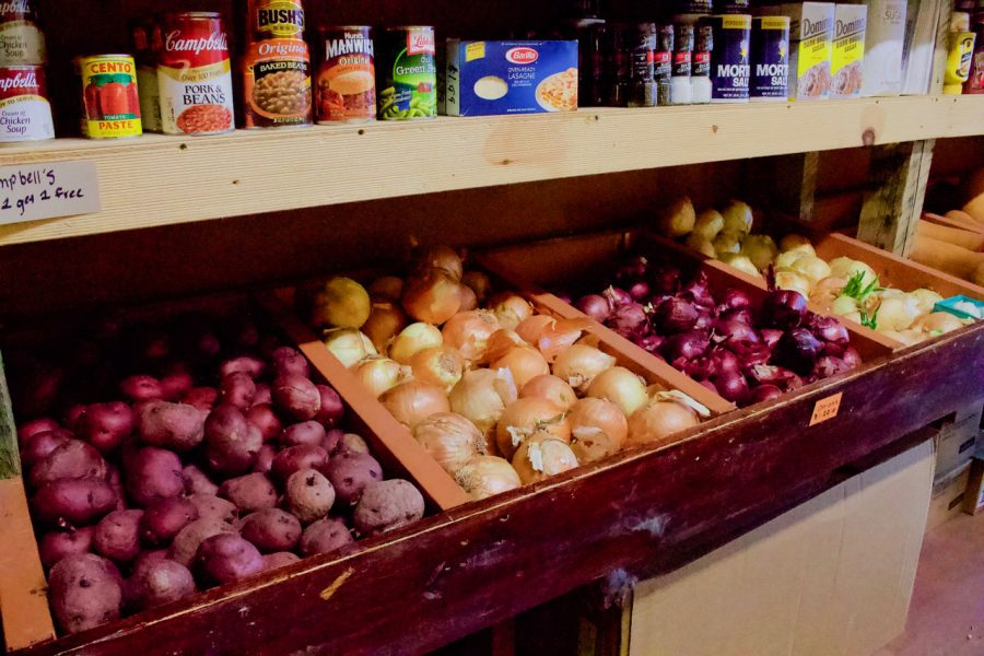 Different varieties of onions and potatoes are displayed under shelves of cans and other non-perishable foods.
