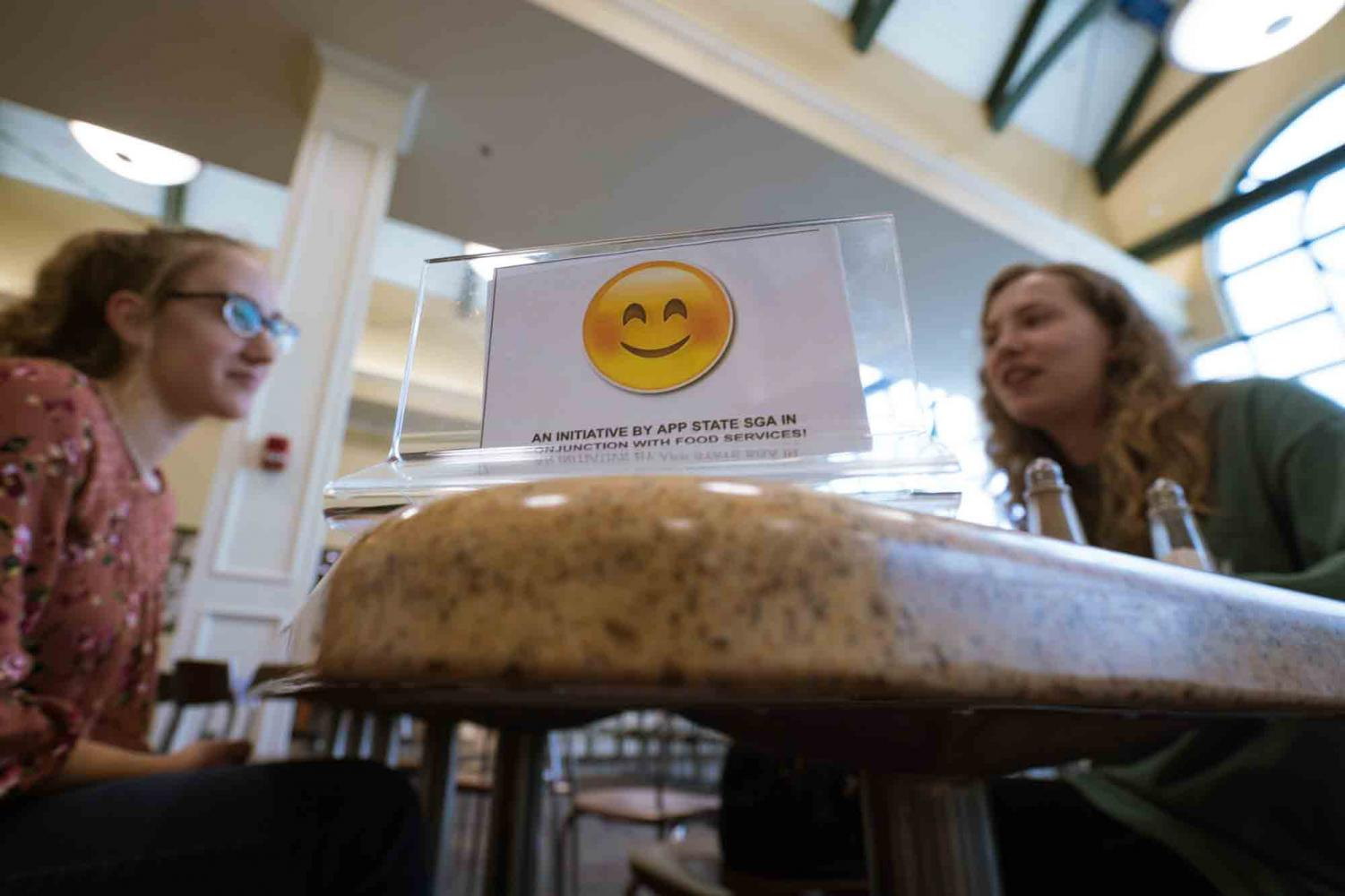 A smiley card brings two students together at lunch in Roess Dining Hall. Former SGA Senator Andrew Strahan created the Smiley Card so that students who don't want to sit alone during meals can place a small card with a smiling emoji on their tables to designate that they want someone to dine with them.