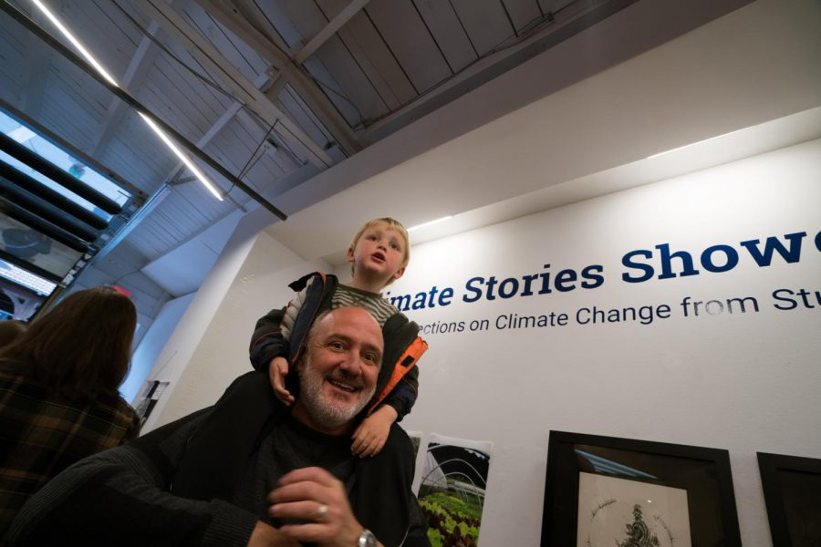 Richard Rheingans, department chair of Sustainable Development, with his son at the Climate Stories Collaborative. The event kicked off Friday at HOW space with the opening of an art installment and several student performances. Photo by Hayley Canal