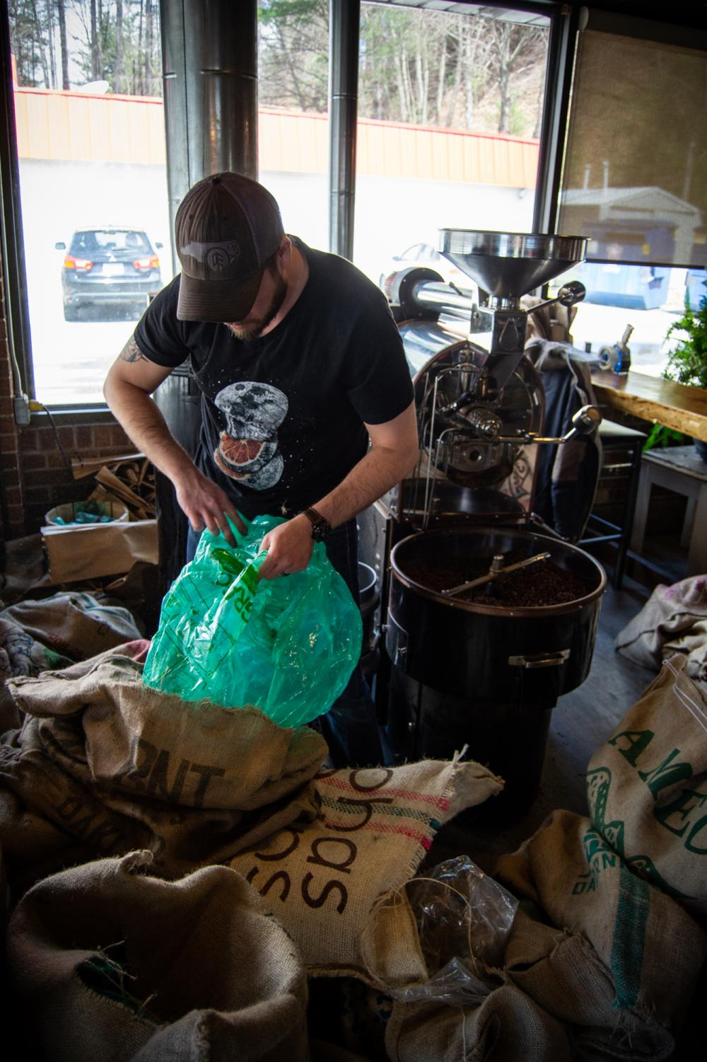 David Tatum siphons through coffee bean sacks behind Local Lion's roasting station. Tatum is the primary roaster at Local Lion Espresso Bar.