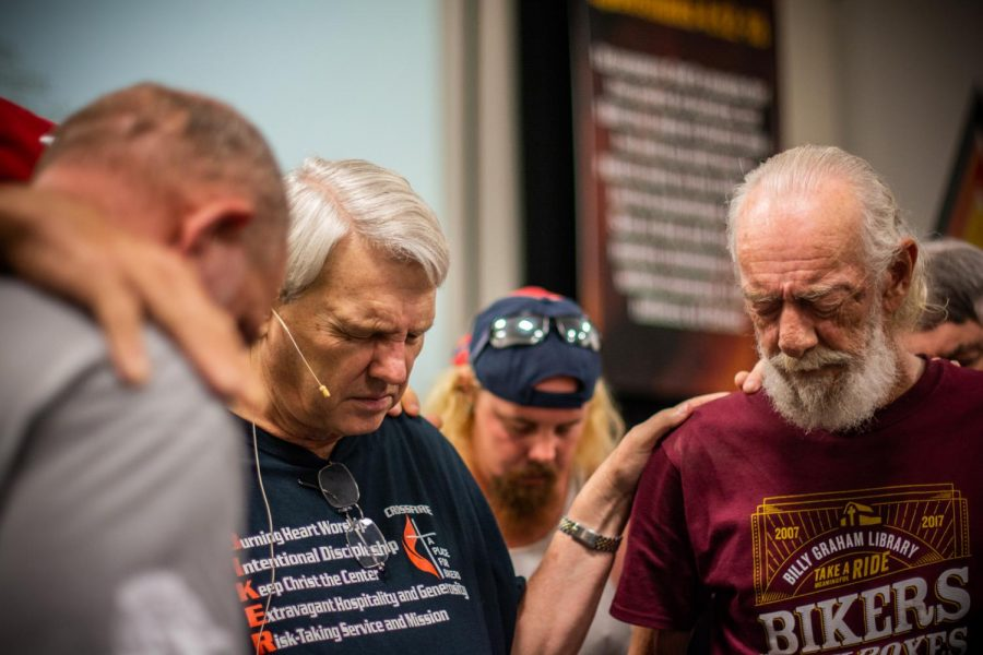 Pastor Alan Rice (left) prays for Kelly Bray (right) during Sunday's group prayer. Bray apparently suffers from hip issues and looked to his church community for hope and good blessings.