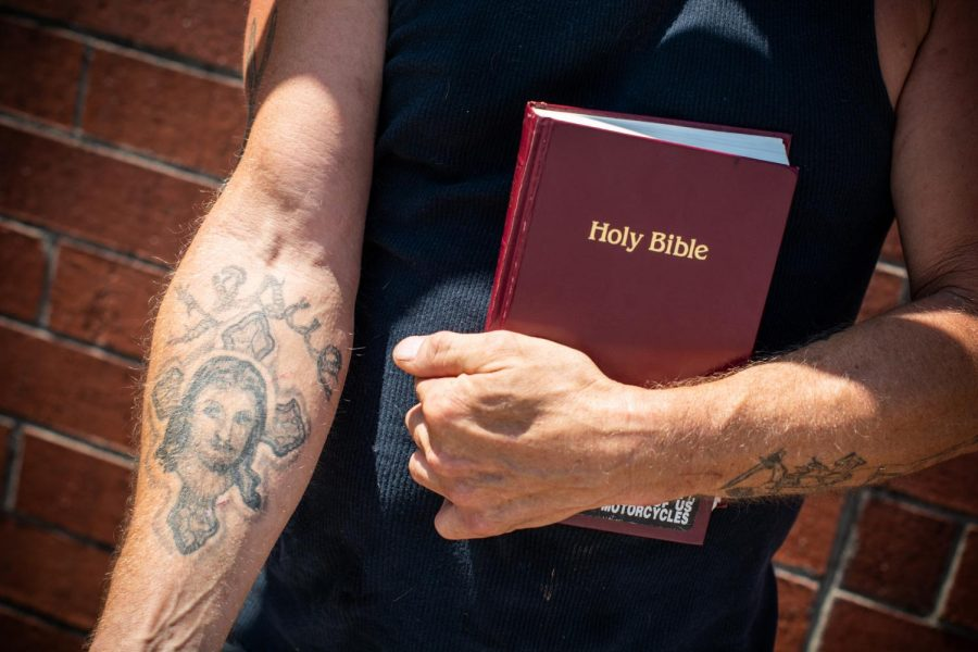 Lee Benge shows off one of his many tattoos. Two of his forearm tattoos depict Jesus in various scenes.