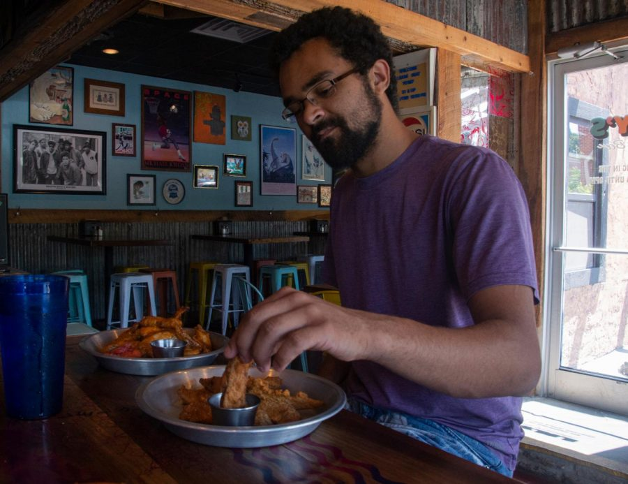 Senior Studio Art major Kelsey Ramsue enjoys some wings and potato wedges at Lily's Snack Bar. The new restaurant is located across from Durham Park on Hardin Street.