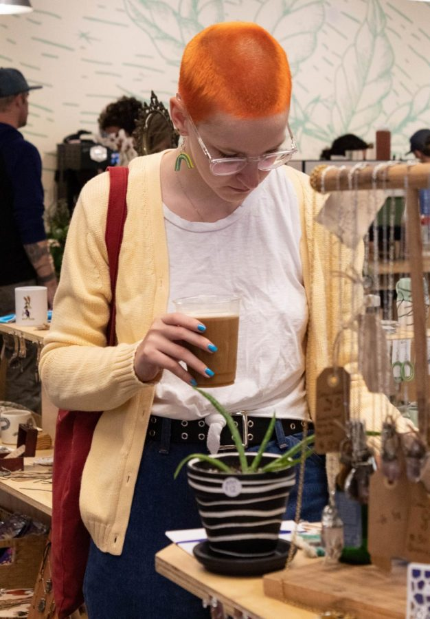 Lizz Henry, a senior religious studies major, sifts through a stand while enjoying her coffee at Pop Up Boone this weekend. The monthly event took place this past weekend at Hatchet Coffee off of Bamboo Road.