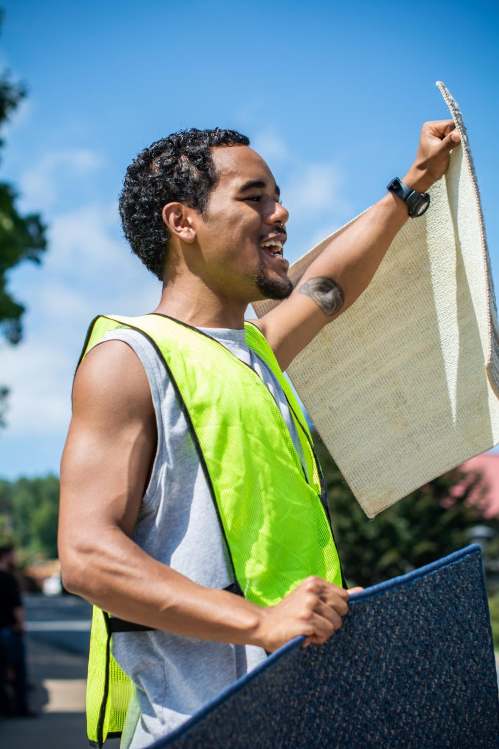 Student+affairs+and+administration+major+Rashaun+Robinson+is+a+first+year+graduate+student+as+well+as+a+volunteer+for+ACT.+Robinson+enthusiastically+helped+sell+rugs+for+the+Carpet+Pre-Sale+during+move-in+on+Friday.