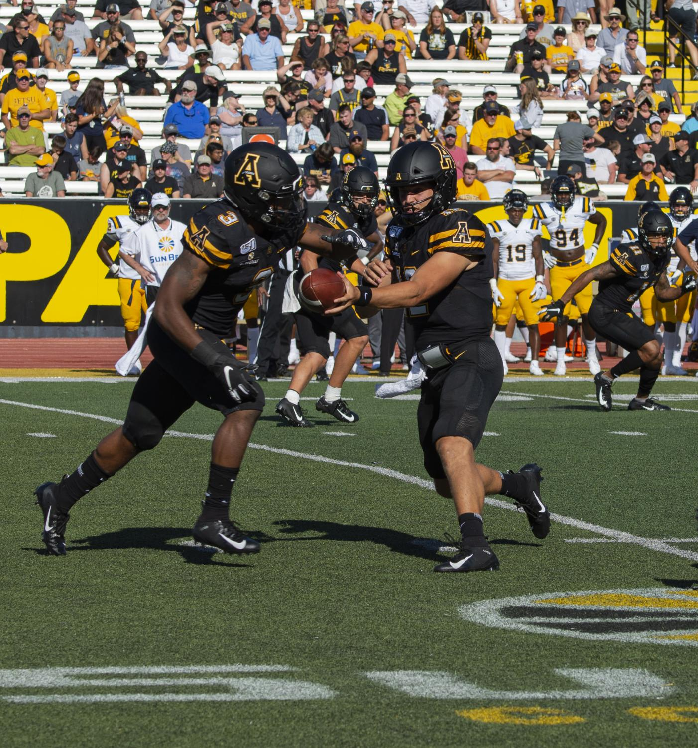Junior running back Darrynton Evans prepares to take a handoff from junior quarterback Zac Thomas in App State's 42-7 win over East Tennessee State on Aug. 31.