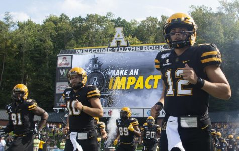Quarterback Zac Thomas, this year's Sun Belt preseason offensive player of year, (far right) leads App State onto the field before a 56-37 victory against Coastal Carolina on Sept. 28.