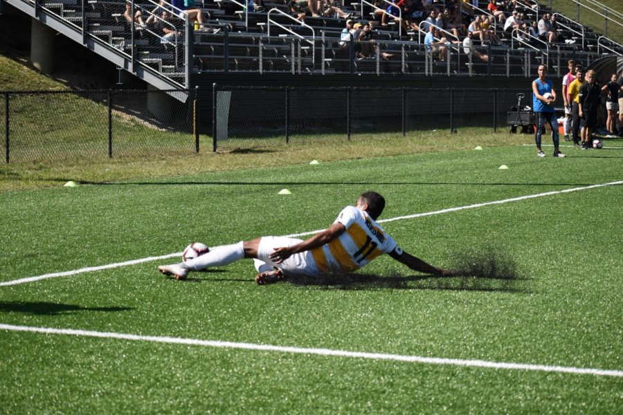 Junior forward Juan Hernandez slides to save the ball from going out of bounds in corner field. Hernandez provided an assist in the sole score that won the Mountaineers the game.