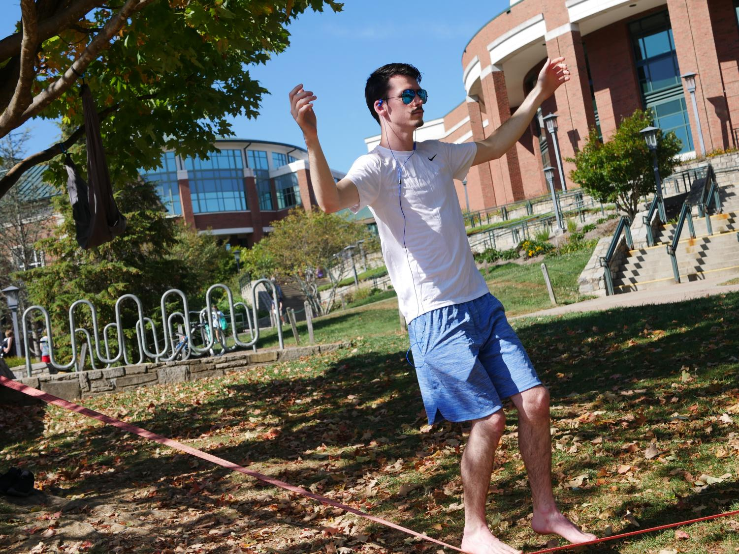 Curt Bridgers, a sophomore computer science major, scales across a popular slacklining spot on Sanford Mall.