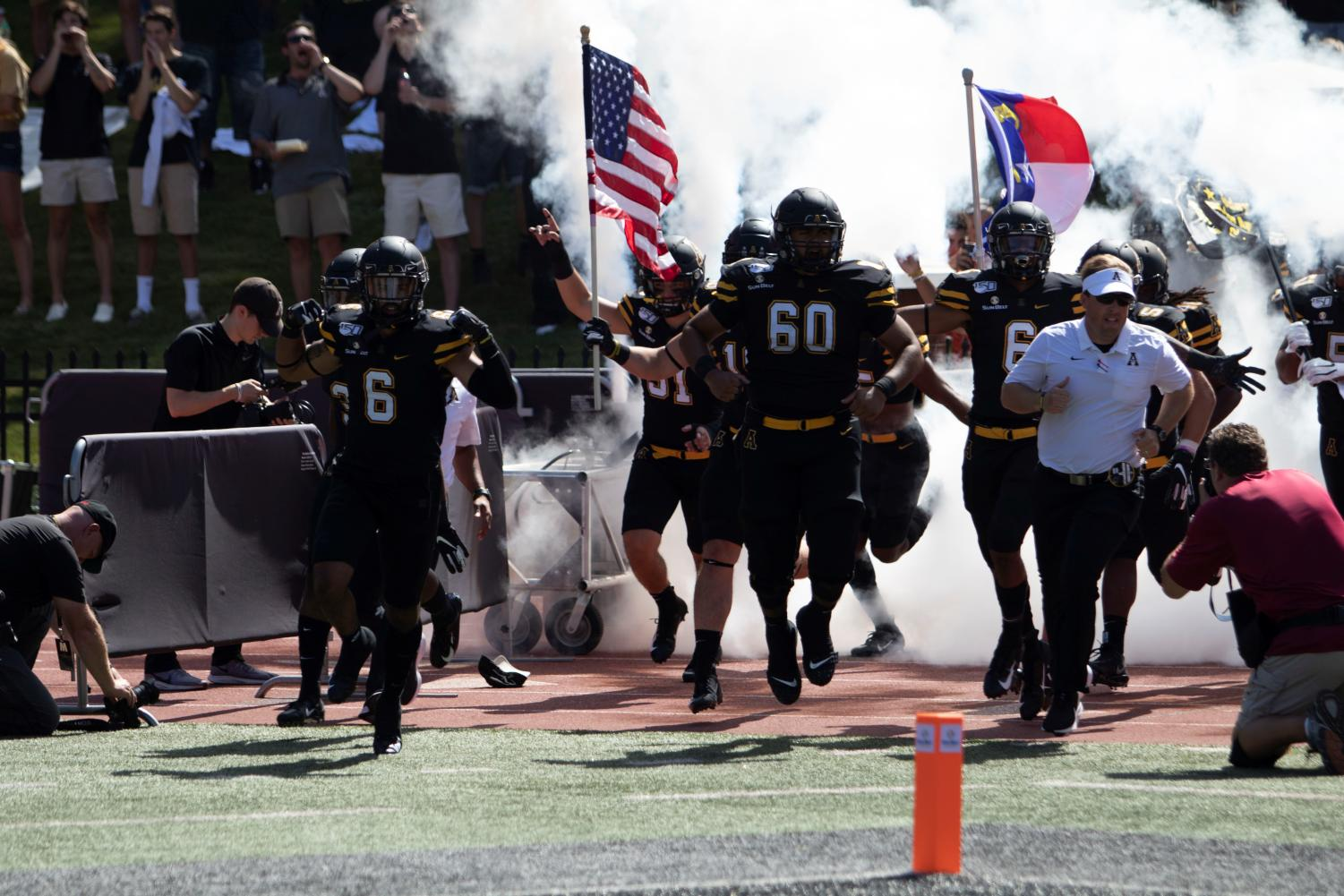 Senior captain & safety Desmond Franklin (left) takes the field alongside junior offensive lineman Noah Hannon (center) and head coach Eliah Drinkwitz (right) before App State's 42-7 victory over East Tennessee State on Aug. 31. // Photo courtesy of App State Athletics