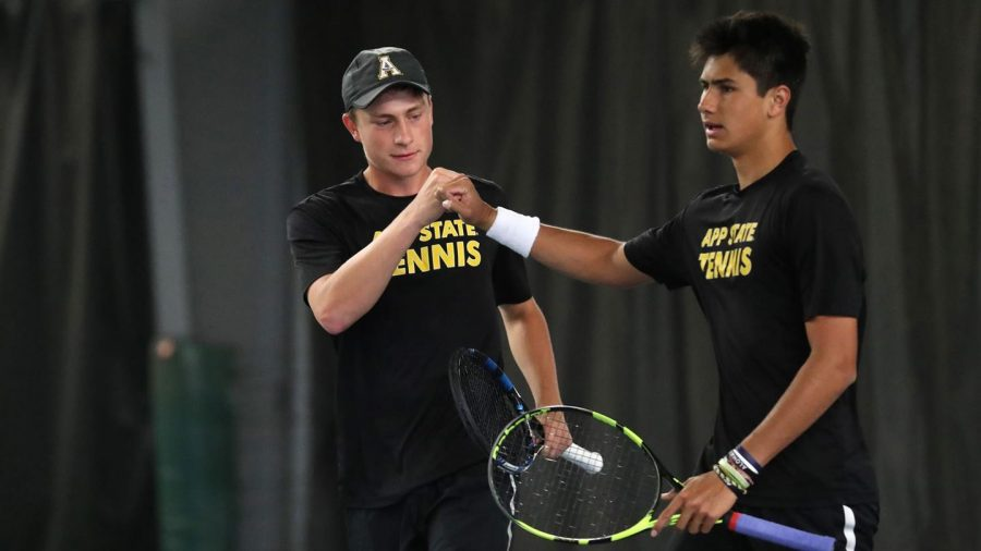 Former App State men's tennis players Milo Bargeron (left) and Zion Heaven (right) fist bump during a match. The App State men's tennis program, along with men's soccer and men's indoor track and field, were discontinued because of budget cuts due to the pandemic.