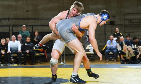 Senior heavyweight Cary Miller takes hold of an opponent from Duke University during their face off on Jan. 24. Mill- er is a Greensboro native and has wrestled since middle school.