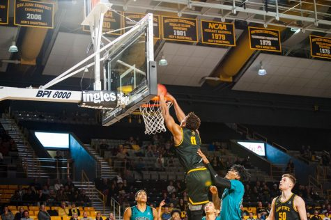 Senior forward Isaac Johnson dunks the ball over a defender in the Mountaineer