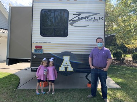 Robert Craven and his two daughters stand outside the RV donated to their family from App State alumnus David Small and his wife, Stacey.