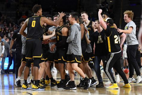 Fist team all-Sun Belt junior guard Justin Forrest celebrates with his teammates after hitting the game-winning three in App State