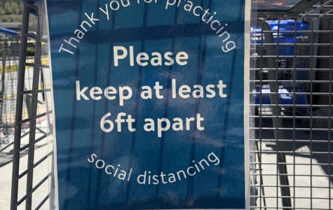 Signs line the carts leading into the Boone Walmart asking people to social distance and remain 6 feet apart.