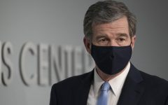 Gov. Roy Cooper dons a face mask at a press briefing.