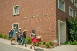 Family and friends assist students moving in to residence halls August 10. People wait outside with items ready to be moved in, following social distancing orders.
