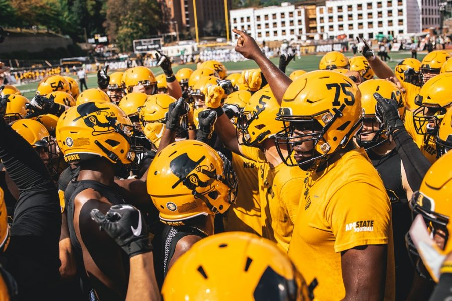 App State players huddle before beating Coastal Carolina 56-37 on Sept. 28. After losing matchups scheduled against Wisconsin, Wake Forest, UMass and Morgan State in 2020, the Mountaineers have added three new non-conference opponents: Charlotte, Marshall and Campbell.
