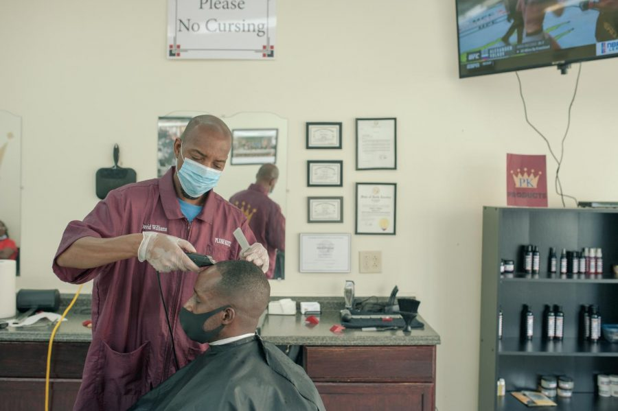 David+Williams+cuts+a+customers+hair+in+Plush+Kutz+barbershop+in+Hickory%2C+N.C.+on+June+19%2C+2020.+Williams+is+a+city+of+Hickory+councilman+and+listens+to+many+voices+as+they+talk+about+%22all+the+world%27s+problems%22+in+his+barbershop.