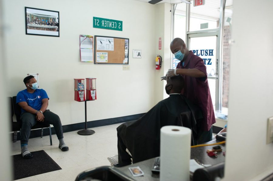 Customers wait in seats along the wall for their turn in the David Williams' barber chair on June 19, 2020.
