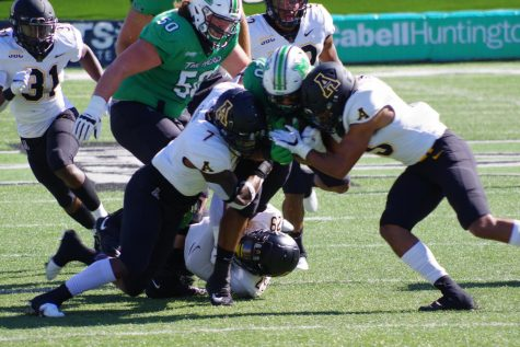 Two Mountaineers combine for a tackle in the 17-7 loss at Marshall Sept. 19.