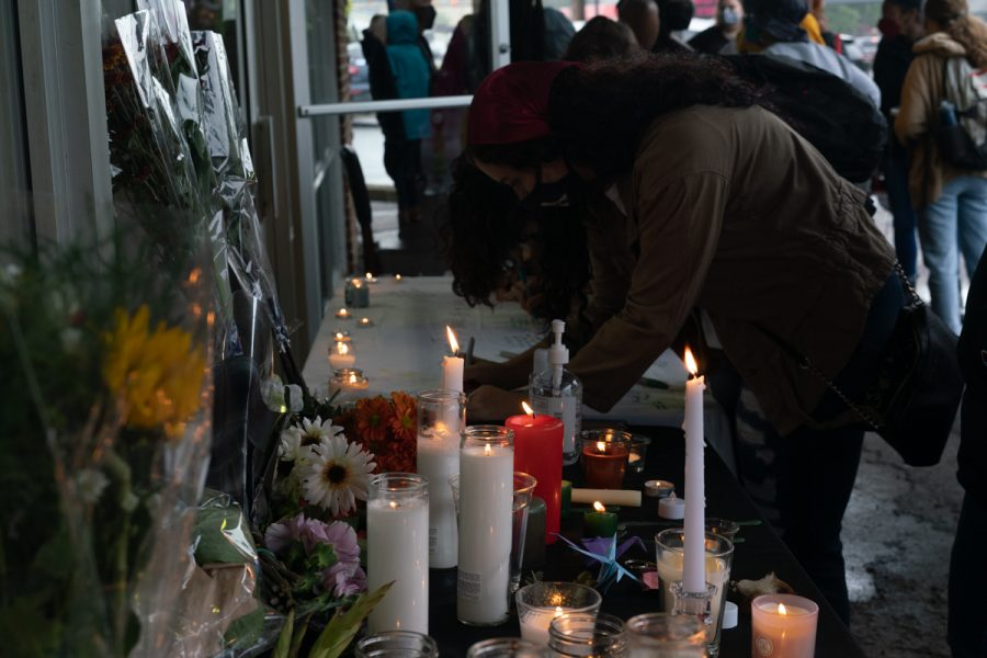 Students and community members lay candles write messages on an altar honoring Breonna Taylor.