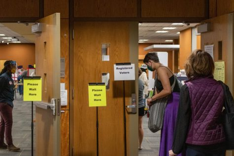 Community members wait in line outside the polling site in the Plemmons Student Union