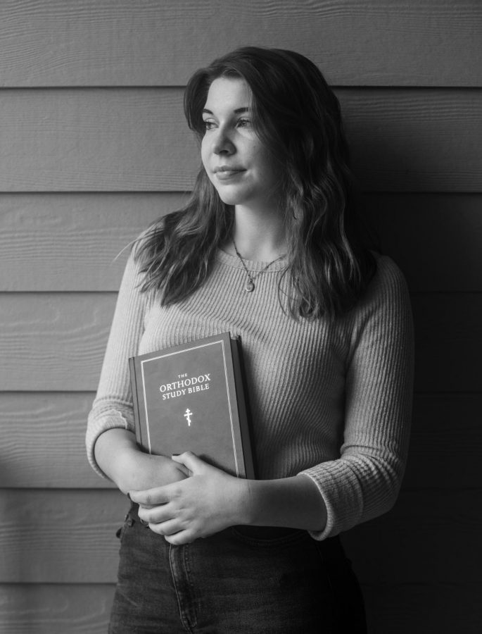 Arianna Moore a junior studying Public Health stands with her Orthodox study bible outside of her student apartment. Moore said her favorite verses are Proverbs 31:8-9.