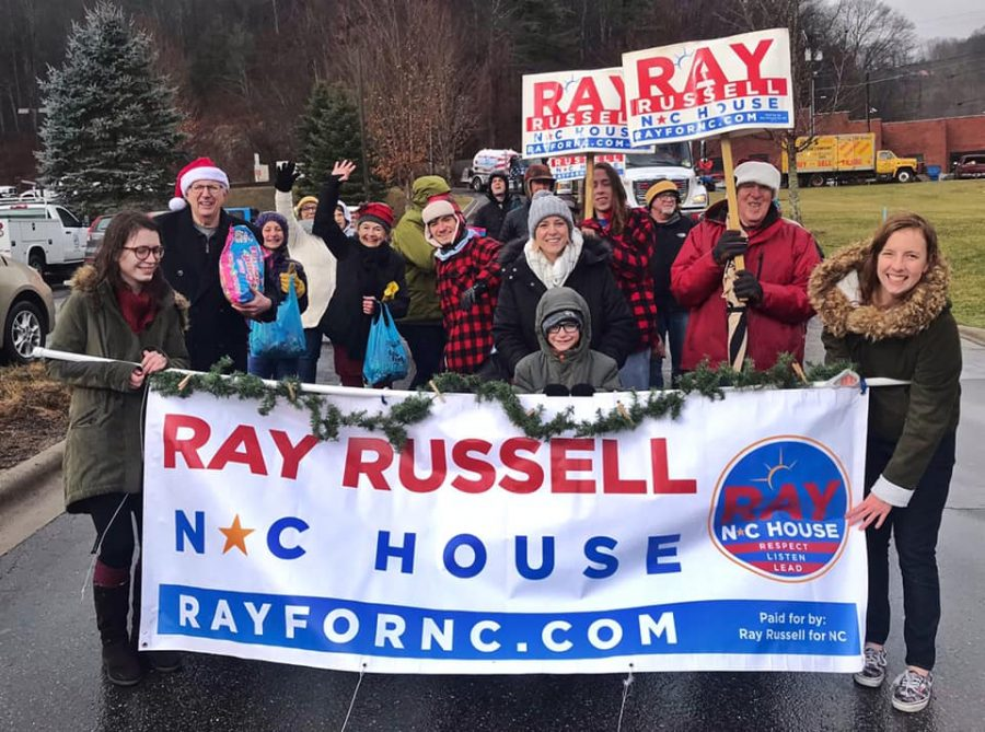 Lee+Franklin+%28pictured+near+the+center%2C+wearing+plaid+jacket+with+a+hat%29%2C+an+App+State+political+science+graduate%2C+campaigns+with+community+members+in+support+of+re-electing+Ray+Russell+%28pictured+at+left%2C+wearing+Santa+hat+and+holding+bag+of+candy%29+to+the+NC+House+of+Representatives.+