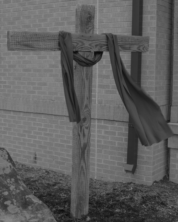 A cross bearing a purple sash outside of the First Baptist Church in Boone.