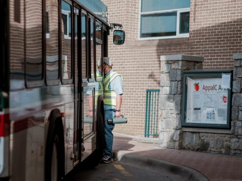 Bus drivers in conversation at the College Street traffic circle. Despite maintaining regular routes and times, AppalCart has seen significantly fewer passengers due to the increasing number of students transitioning to online learning.
