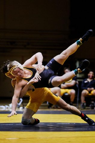 App State freshman Tommy Askey (gold) puts a move on fellow freshman Tristan Pugh (black) at the annual Black and Gold Intrasquad scrimmage Friday at Varsity Gym in Boone.