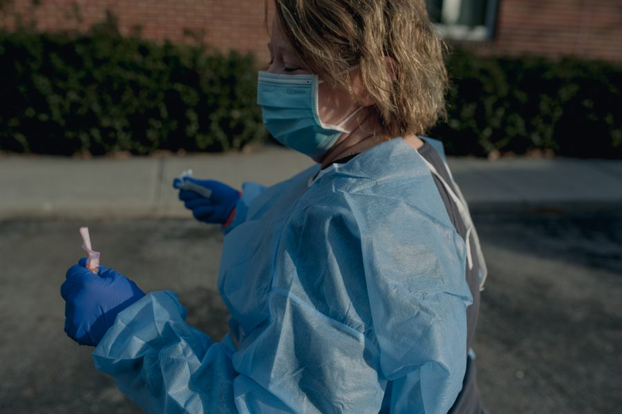 Robin Overbay carrying away a used COVID-19 vaccine after administering to a patient in the parking lot of AppHealthCare.