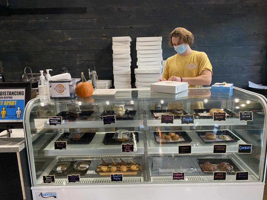 Nick Cellini prepares an order behind the counter at Hole Lotta Doughnuts on King Street. The West Jefferson-based shop opened this fall in Boone after popular demand from customers.