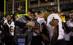 App State head coach Shawn Clark hands sophomore running back Camerun Peoples the Myrtle Beach Bowl MVP trophy after his record-setting performance Monday.