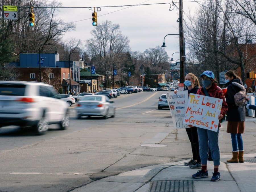 Three anti-abortion protestors stand on the corner outside Mellow Mushroom across from the Watauga County Government complex. One protestor wears a hat from the Hope Center, a faith-based crisis pregnancy center on Howard Street. Crisis pregnancy centers provide support for people with unplanned pregnancies, but draw criticism for dissuading people from seeking abortions.