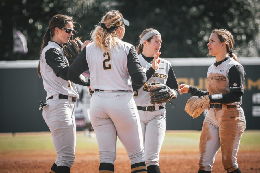 Members of the App State softball team convene in the infield during a game against Oakland last season. Before the pandemic interrupted their season, the Mountaineers were 13-9, including a 1-0 shutout of Virginia to open the year.