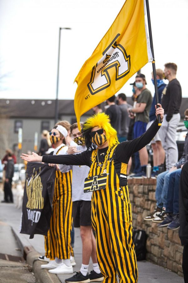 The Band of Bibbed Boonies stands with fans as they welcome the new Sun Belt Conference champions, App State's men's basketball. The group comes to the majority of App State sporting events in their black and gold overalls.
