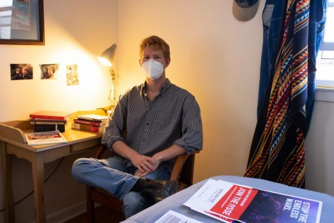 Lachlan James, head of the App State Chapter of IYSSE sits in his bedroom with hisi collection of literature and signage related to the world views represented in the organization.