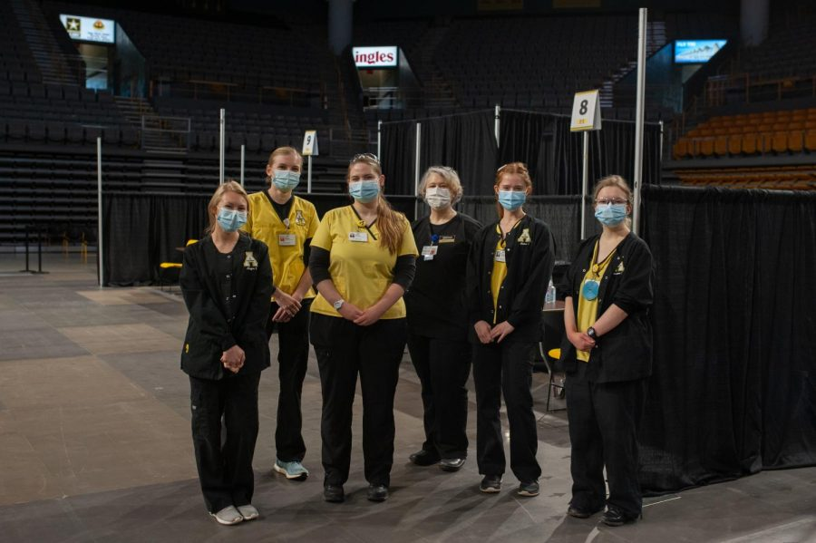 A group of nursing students administering J&J vaccines pose for a portrait.