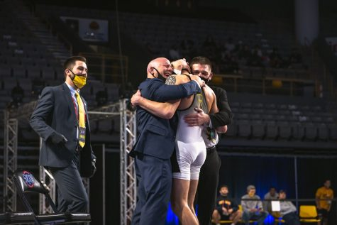 App State redshirt junior Cody Bond embraces head coach JohnMark Bentley and assistant coach Ian Miller after winning an individual SoCon title on Sunday night in Boone. Bentley said part of the reason the match was so emotional was because of how far Bond has come on his journey at App State.