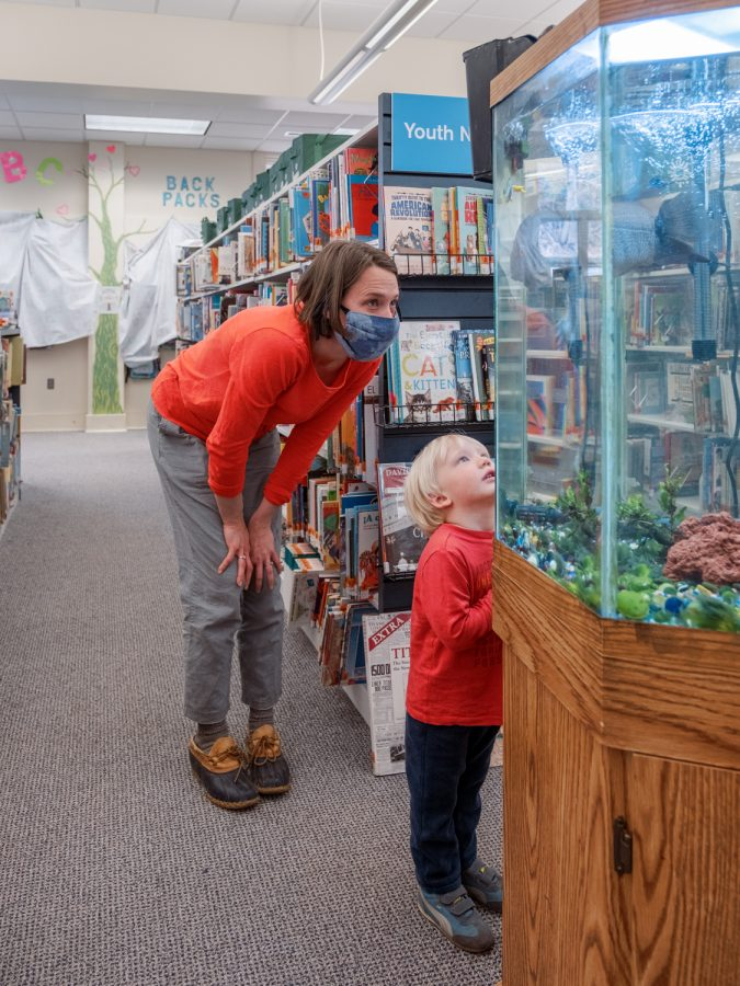 Among the most excited to see returning patrons is the resident pet fish, seen here inspecting a parent and child in the library.