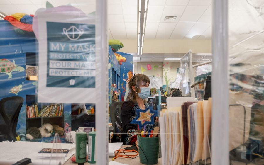"""It's been like a little reunion"": Judith Winecoff, youth services librarian at the Watauga County Public Library, works at her desk behind plexiglass dividers to protect both employees and returning library patrons from COVID-19."