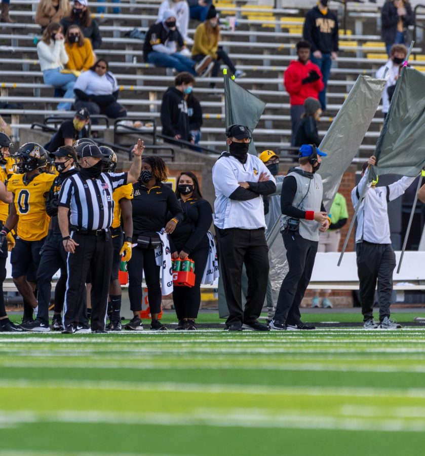 "App State head football coach Shawn Clark (white shirt, black cap and gaiter) coaches during App State's win over Georgia State Nov. 14 in Boone. Since last March, all NCAA recruiting has been virtual, but on June 1, coaches can return to in-person recruitment. ""It'll be good to see a kid in person, see what he's made of, see who his parents are and get a feel for them,"" Clark said."
