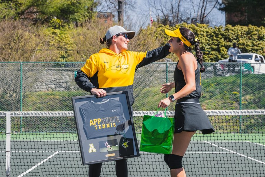 App State senior women's tennis player María Zacarias (right) embraces assistant coach Miller Hales (left) on Senior Day against South Alabama April 4 in Boone. Zacarias and freshman doubles partner Ksenia Aleshina won their match 6-2.