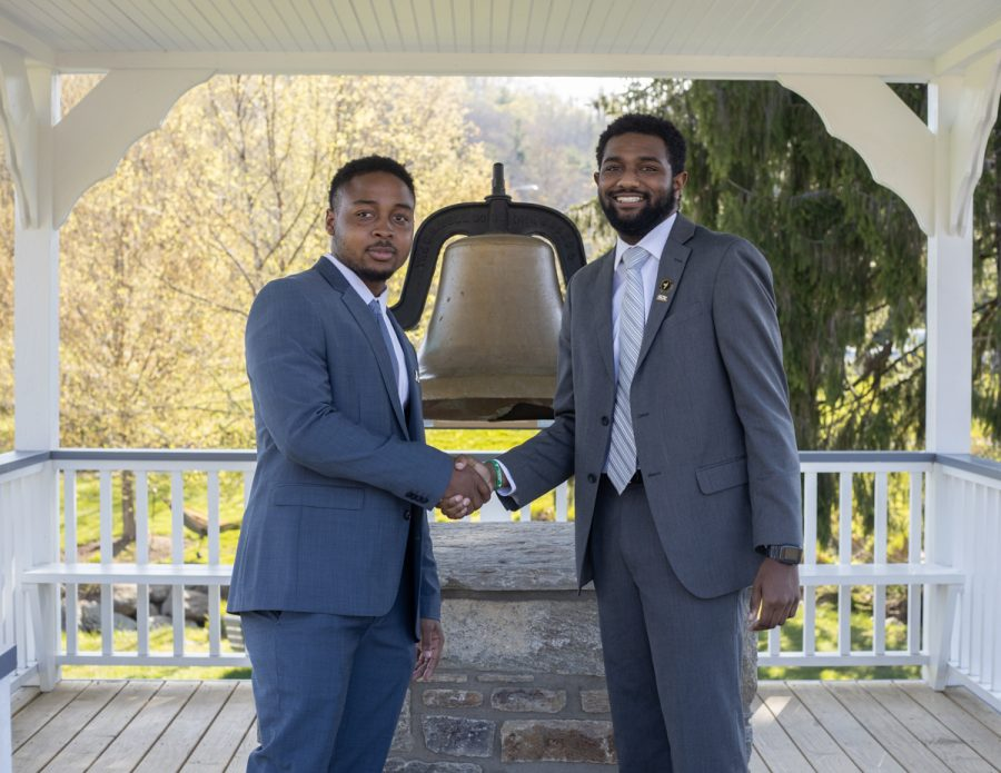 Gardin, right, and Evans, left, shake hands in front of the Founder's Bell in Durham Park to commemorate the beginning of their term as student body president and vice president.