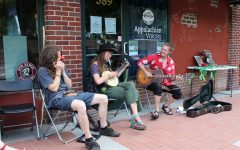 Jacob Moore (left) and Alex Woodbury (right), joined by a third musician, performing outside of the art market.