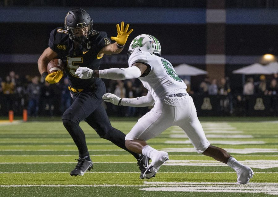 Super senior receiver Thomas Hennigan stiff arms a defender on one of his nine receptions on the night. Hennigan caught nine of his 10 targets, racking up 123 receiving yards against the Thundering Herd.