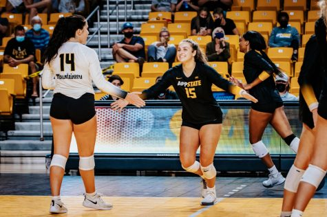 Senior Grace Kinsch celebrates with her teammate, grad student Emma Reilly, who has the fifth most digs in program history.